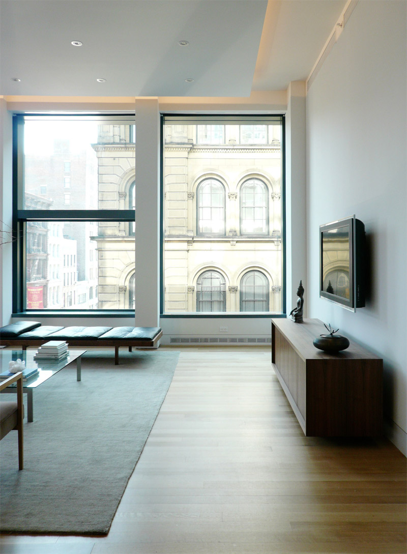 Minimalist Modern Apartments In New York City With Twin Windows Organizer Sliding Windows Combined Black Sofas Bed And Low Glass Table In Gray Rug Featuring Rectangular Wooden Storage Under Mounted Wall LCD TV On Gray Walls Also Wooden Laminate Floor
