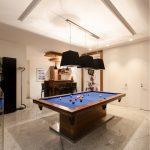 billiard room with elegant black pendant lamp wooden minuibar brown wooden barstool