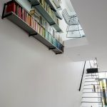 brown-stained-wooden-floor-black-vernished-wooden-stairs-glasses-ceiling-chrome-aliminium-bookshelf-modern-aluminium-chair