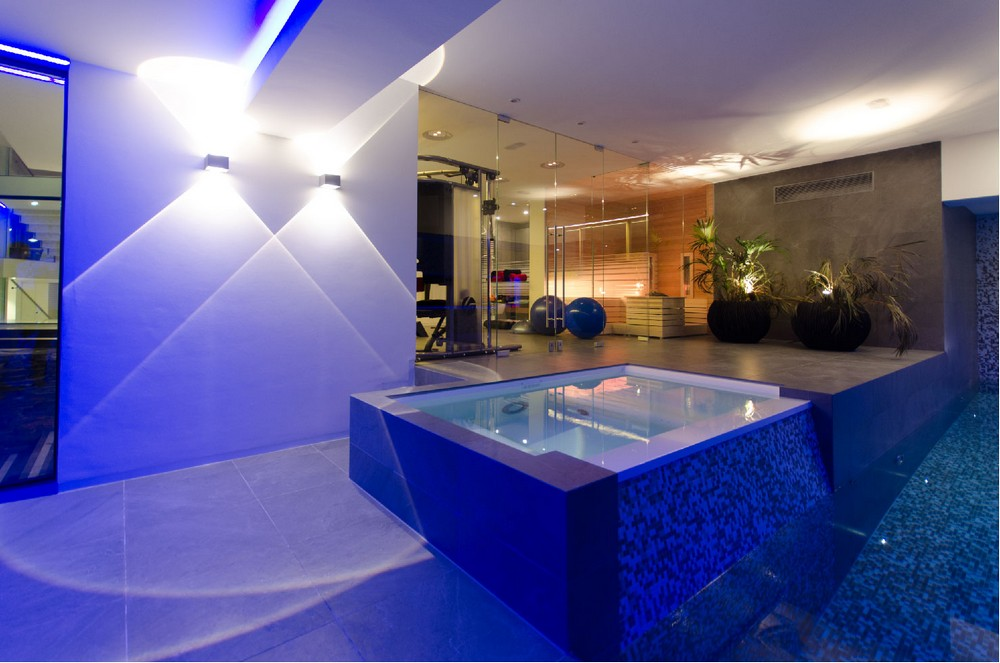 Elegan jacuzzi with blue lighting fitness room with glasses wall indoor swimming pool with blue light elegan lighting architectural minimalist home design