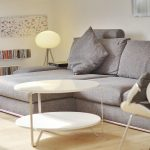 Grey Fabric Puffy Sofa Bright Floor Lamp Wooden Classic Radio White Wooden Bookself Little Square Cushion Brown Wooden Floor White Oval Table White Living Room Chair Fury Rug Abstract Painting