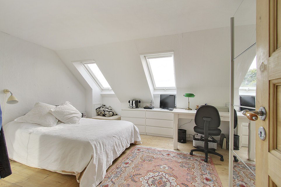 sloping-ceiling-square-glasses-windown-greed-floor-lamp-cream-coloured-arch-lamp-a-comfy-white-bed-white-square-pillow-double-square-glasses-window-21inch-monitor-white-varnished-wooden-desk-black-swivel-chair-colorful-fur-rug-brown-wooden-door-green