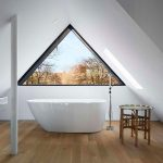 white-minimalis-bathtub-sloping-celing-modern-chrome-shower-glasses-penthouse-brown-stained-wooden-floor-brown-vernished-bamboo-table