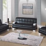 Classic Black Coloured Leather Sofa Set In Trendy Dwelling Room With Grey Painting Wall Also Oval Glass Table On White Fur Rug And Picket Floor Together With Glasses Window Corner