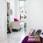 White varnished wooden Bookshelf Beside White Sofa And Pink Cushions Synthetic Flowers Purple Color