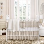 White-wooden-crib-white-wooden-shelf-white-wooden-cabinet-white-armchair-white-curtain-white-framed-mirror-light-brown-patterned-rug-cream-painted-wall-brown-patterned-bed-sheet