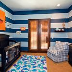 amazing blue stripes nursery room with traditional black crib and square patttern chair with fish motif rug and elegant wooden cabinet with large door design in large carpeting