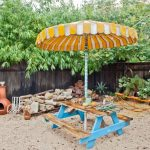 amazing raw wood and turquoise table and chair orange seesaw white sandy ground orange and white patio umbrella dark and light brown  wood fence blue and white striped umbrella pole
