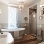 amazing small bathroom design with gorgoeus crystal chandelier and elegant white bath tun also round washbow and ecletic wall light in hardwooden flooring