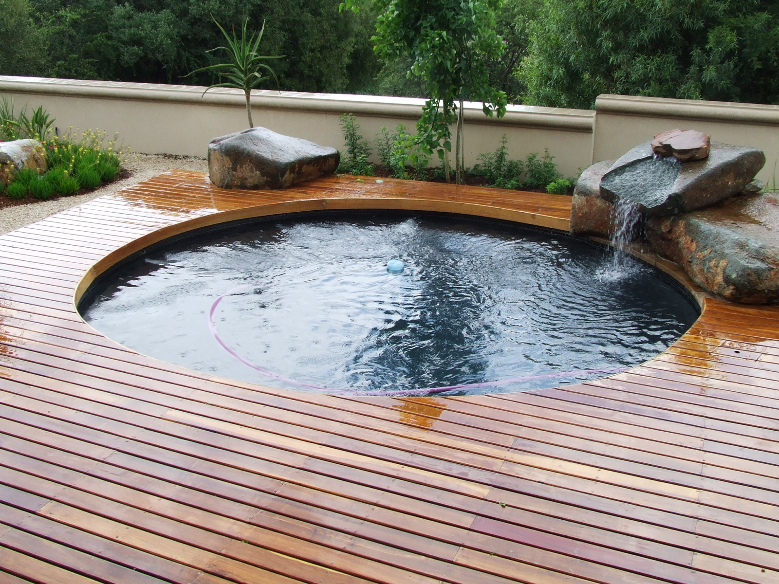 Amazing Small Swimming Pool With Round Design And Magnifceint Wooden Pool  Deck And Gorgeous Stone Waterfall