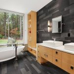 beautiful black bathroom with natural wooden black wall panel also ravishing soft cream cabinate storage and elegant white sink and bathtub in hardwooden flooring idea