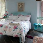 beautiful blue bed comfy pillow elegan bedroom floor flower pinting on the wall