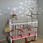 beautiful grey wall with white sakura tree mural white crib with red ribbon decoration yellow patterned curtain light brown wall-to-wall carpetting colorful fabric bedding set