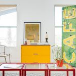 beige ceramic flooring glass table with red frame white wall white string chair lave lamp with black frame yellow cabinet unique yellow cafe sign with green background tall window with white frame