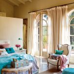beige high beamed ceiling beige arched windows beige curtains white brick wall brown and white rug white armchair turquois blanket blue and white bed cover colorful pillows