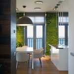 Biotic Living Garden White Painted Ceiling Wooden Floor White Dining Table White Armchairs Dark Wooden Varnished Wall White Painted Countertop Minimalist Pendant Lamp Brown Pendant Lamp