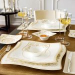 black dining table cream dining chair fold table cloth wine glasses beauiful white and gold plate set white wall black round table silver candelabra hardwood flooring