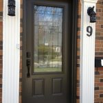 black framed door with glass center stylish black wall mounted lantern white posts brick front wall simple black house number classic black doorknob