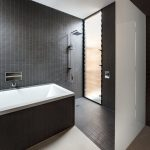 black tiled wall built in bathtub covered with black tiled white glass separator single steel shower