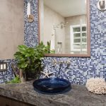 blue mosaic tiled backspalsh framed hanging mirror blue vessel sink single steel faucet minimalist wall sconce lamp granit countertop porcelain tiled wall white reef decoration white starfish decoration
