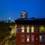brick wall apartment 5 floored apartment Sarah Roosevelt night view high building blue twilight sky modern apartment luminous New York city