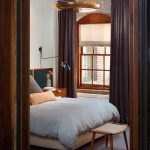 brick wall brown window curtain white bedspread wooden coffee table round golden pendant lamp wooden framed sliding window industrial design modern bedroom arched wall mounted lamp