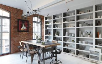brick walls white painted ceiling white painted wooden floor industrial metal pendant lamp dark gray metal dining chairs metal  dining table built-in white painted open storages white metal ladder