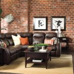 bricked wall dark brown leathered sofa dark wooden bileved sidetable dark wooden bileved coffee table black painted wooden floor dark wooden storage rattan rug tidy living room