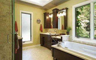 bright color painted wall light marble floor dark wooden bathroom cabinets undermount sink skylighted ceiling white bathtub cozy bathroom ideas warm tone bathroom