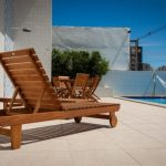 brown Wooden varnished Sundeck idea With Wheel In Trendy Fashionable Swimming Pool