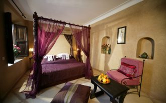 brown wall white ceiling purple chair black table dark purple pillow wood windows white gold table lamps purple mosquito net purple bed set black wood canopy bed flowers wall decoration