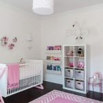 chic baby girl room with elegant white crib and interesting wall mount bookshelves also large decorative cabinet with pinky tribal rug and wonderful white pendant in glossy laminate flooring