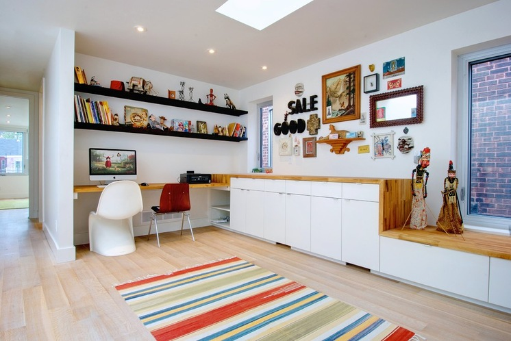 colorful stripped rug white stain wood cabinet wood desk brown chair white chair white wall white ceiling skylight white windows frame black hanging shelves