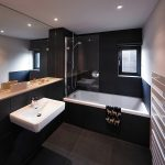 contemporary black bathroom with elegant white sink and bathtub also wonderful large mirror creating larger illumination in granite black flooring