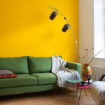 contemporary brown floor lamp dark green sofa sunny yellow wall white wall pink small table turqoise table white windows white green patterned armchair brown flower painted vase
