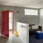 contemporary entrance white ceiling white wall grey with white strained wall white low panel concrete flooring red door blue ottoman table navy carpet black sofa white and grey striped pillows