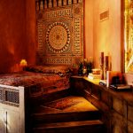 creame painted wall mediterranian patterned rut patchworked bedspread rustic wooden cabinets wooden vintage bed vintage small night lamp
