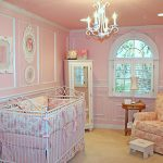 cute pink baby nursery room with iron white crib and gorgoeus chandelier also amazing flower patern sofa feat white framed window and large carpeting