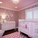 cute pink themed nursery pink ceiling with white trim white blind white framed window dark brown tile flooring white dresser pink patterned wall paper white crib beautiful white ceiling lamp
