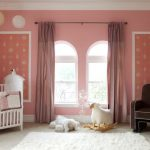 cute pink wall white framed windows white fur rug ceramic flooring pink curtain dark brown armchair ahite crib white ceiling animal doll white bed sheet