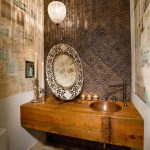 dark brown terracota tile wall vintage wallpaper rustic wooden panel marble tile floor drop in vessel sink single faucet round framed standing mirror crystall pendant lamp vintage candlestick