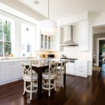 Dark Wooden Floor White Painted Kitchen Cabinets White Marble Kitchen Countertop White Simple Pendant Lamp White Painted Ceiling Dark Wooden Dining Table White Painted Wooden Framed Window Bright Kitchen