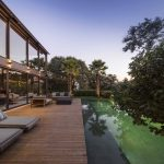 deck in swimming pool wooden deck floor gray outdoor chairs large glass panel green vegetation beautiful sky geometric house Limanto Residence in Sao Paolo Brazil