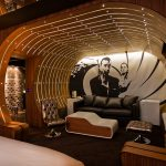 eclectic room interior for hotel with james bond wall painting also magnificent wooden wall panel with dramatic ceiling lamp also cozy black leather sofa in hardwooden flooring
