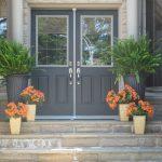 elegant black framed window with light grey trims big black pot light brown small pot light grey window frames stone stairstone tile front wall