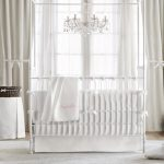 elegant white chandelier wood floor white soft rug white armchair white wall white framed mirror white curtain white framed window white crib white wardrobe