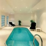 enchanting small indoor swimming pool and interesting lounge chairs with eccentic multiple downlight in marble flooring