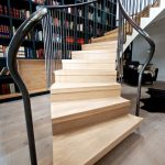 english oak treads engliah oak risers black leathered handtrails steeled balustrade uprights black pianted bookcase light wooden floor black furry rug whirling staircase urban staircase design
