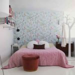 floral wallpaper white painted wall large bed tree shaped hanger white ceramic tiled flooring white iron framed bookshelves red upholstered stool dark wooden storages steel standing lamp