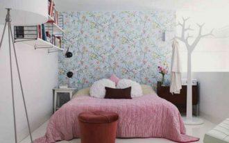 floral wallpaper white painted wall large bed tree shaped hanger white ceramic tiled flooring white iron framed bookshelves red upholstered stool dark wooden storages steel standing lamp